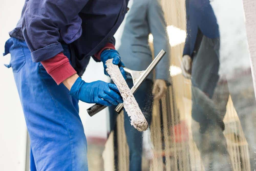 Fensterputz Sets im Einsatz: in Arbeitskleidung im beim Fenster putzen