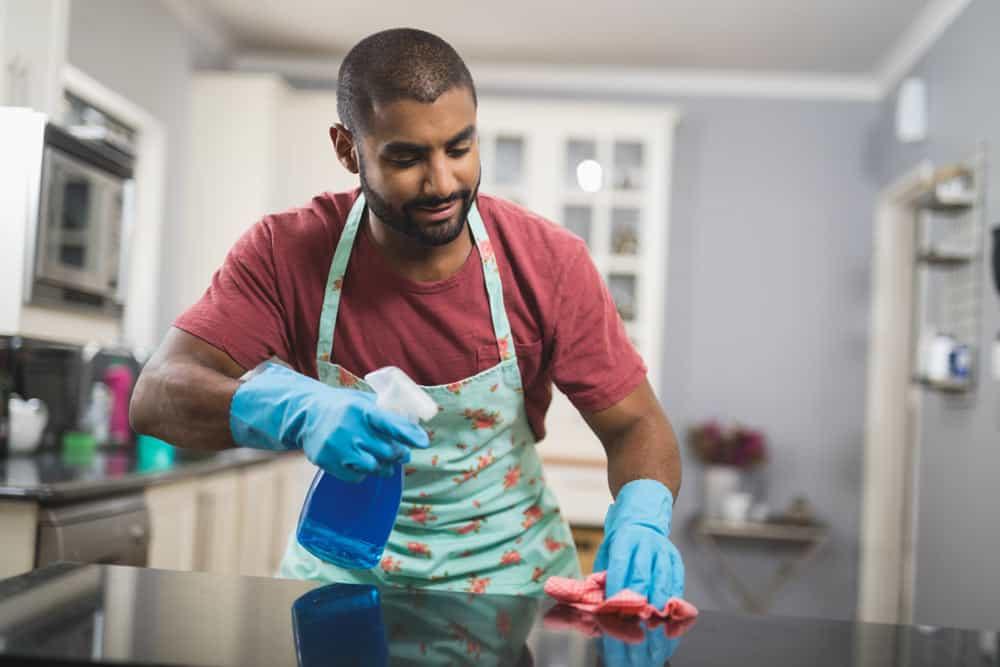 Mann beim reinigen einer Marmorplatte in der Küche