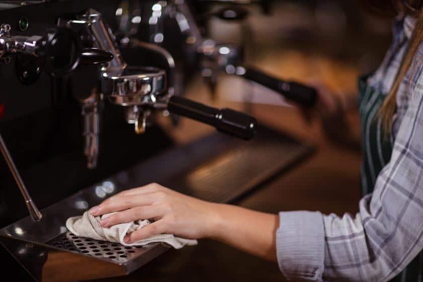 Frau am Kaffeemaschinen reinigen mit Tuch