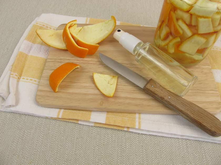 Allzweckreiniger selber machen aus Zitrusschalen. Brett mit Schalen und Glas.