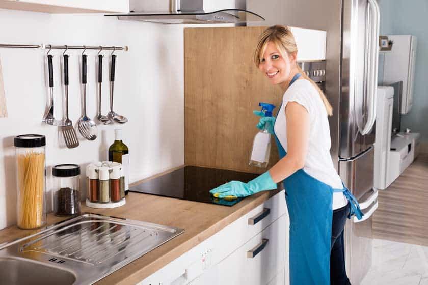 Frau reinigt Dunstabzugshaube in der Küche