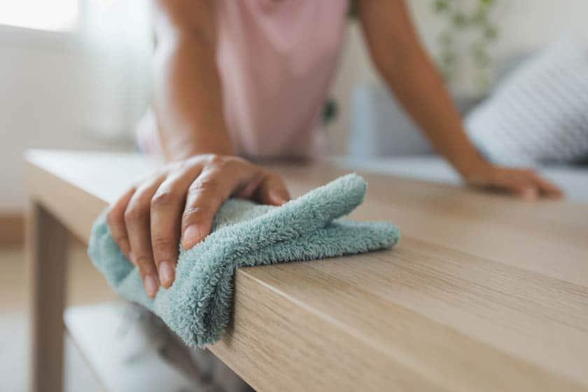 Hand mit Putztuch wischt über Holztisch