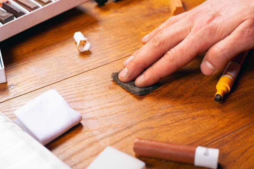 Hand auf Tisch zeigt wie man Wachs auf Holz entfernt